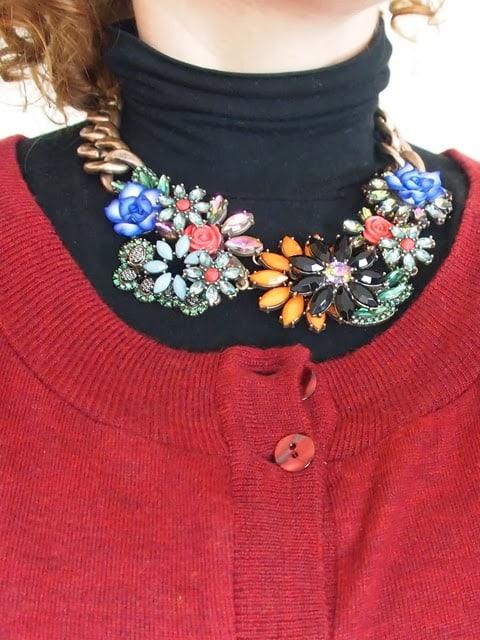 verdementa_blog outfit con gonna longuette in ecopelle, maglia poncho, stivali col tacco e collana fiori Zara.